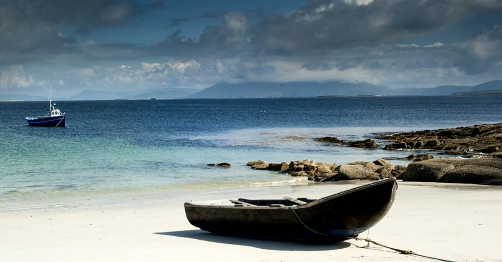 A traditional curragh boat on a white sand beach in Co. Mayo, Ireland