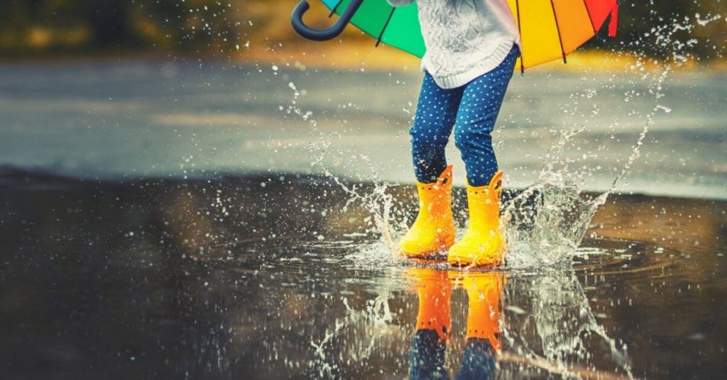 A girl having fun jumping in a puddle of water.