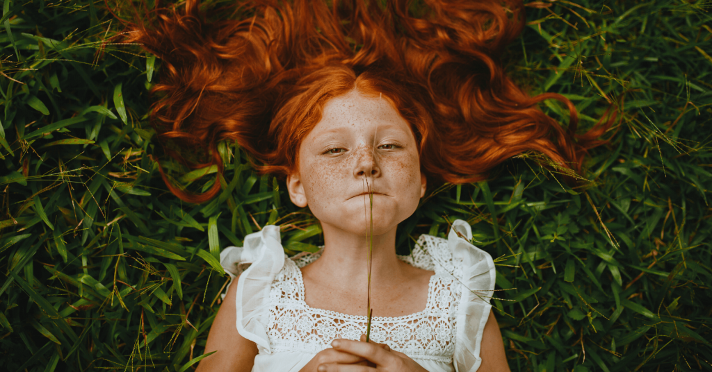 Girl with red hair on grass